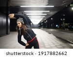 Female stretching her left side before her night jog in the city