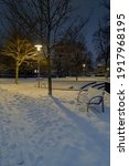 Snow Covered Park With Benches...