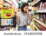 Small photo of Consumption And Consumerism. Portrait Of Young Woman With Shopping Cart In Market Buying Groceries Food Taking Products From Shelves In Store, Holding Glass Jar Of Sauce, Checking Label Or Expiry Date