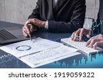 Small photo of Two traders man and woman researching historic data to predict stock market behavior. Internet trading concept. Forex and financial hologram chart over the table with the documents