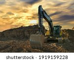Small photo of Excavator working on earthmoving at open pit mining on sunset background. Backhoe digs sand and gravel in quarry. Heavy construction equipment during excavation at construction site