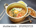Korean style instant noodle, Ramyeon with egg yolk, chilli, kimchi vegetables pickled and radish pickles in a traditional korean noodle pot.