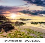 calm sea with some wave attacks the sandy beach with boulders and seaweed and break on them at sunset - stock photo
