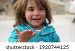 Small photo of Aarsal, Beqaa Lebanon - 2 20 2021: Syrian Refugee Poor Little Girl portrait in Refuge Camp at Syrian Lebanese Borders Laughing   Happy expressions Face
