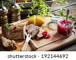 Closeup of venison with cranberry sauce and vegetables - stock photo