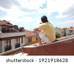 A Young Man Sitting On The Roof ...