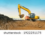 Small photo of A large construction excavator of yellow color on the construction site in a quarry for quarrying. Industrial image.