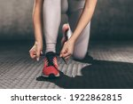 Small photo of Closeup of young woman runner tying her shoelaces.