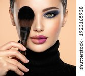 Small photo of Portrait of a girl with cosmetic brush at face. Woman covering one eye on the face using makeup brush. One half face of a beautiful white woman with bright makeup and the other is natural.