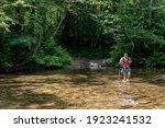 Woman Wades Through Wide Creek...
