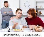 Small photo of Senior woman calming chagrined girl during her quarrel with boyfriend