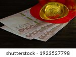 Small photo of Piece gold and Thai cash in red envelope or gratuity in new year chinese day called *Angpao* on brown wooden background , Select focus, (Chinese Language, meaning rich and lucky), space for text
