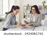 Small photo of Happy female client signs a lease or purchase agreement given to her by a bank manager or real estate agent. Before signing the woman reads the terms of the mortgage, lease or purchase agreement.