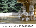 Architectural elements of a fountain in the form of satyrs playing on flutes. Fauns and lions marble statues as part of a fountain in the city park of Almaty, Kazakhstan, in summer. Satyr Fountain.