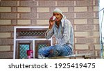 Small photo of 24 February 2021-Khatoo, Jaipur, India. Man with tea. Professional painter redo a living room, have a rest with a cup of tea. Adult sitting on ladder among paint tools and accessories during the break