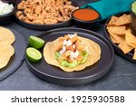 Small photo of Mexican pork rind (chicharron) taco with guacamole and onion with a garnish of lime on a black plate, Mexican food in the background as a plate of pork rinds, tortillas, and sauces to go with it.