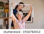 Small photo of Young trainer helping senior woman with resistance band. Lovely physiotherapy health worker exercise with old woman at home. Happy smiling senior woman using rubber band to improve her muscle tone.