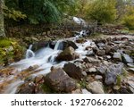 Waterfall And Wooden Bridge At...