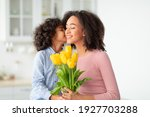 Small photo of I Love You, Mommy. Portrait of cute African American girl kissing her mum in cheek and giving bunch of yellow tulips flowers, greeting woman with holiday, Women's or Mother's Day or birthday.