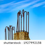 Small photo of Rusty, metal hooks on top of a concrete, steel reinforced beam, have been abandoned decades ago, as the building project faltered, and now simply stick out against the backdrop of a cloudy, blue sky.