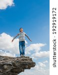 Small photo of teenager suicide acrophobia boy man stands on precipice cliff height and fear heights on a background of blue sky