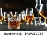 Small photo of Hard strong alcoholic drinks and distillates in glasses in assortment: vodka, cognac, tequila, scotch, brandy and whiskey, grappa, liqueur, vermouth, tincture, rum. Brown background
