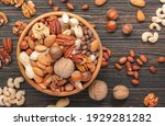 Small photo of Assortment of nuts in bowls. Cashews, hazelnuts, walnuts, pistachios, pecans, pine nuts, peanuts, macadamia, almonds, brazil nuts. Food mix on wooden background, top view, copy space
