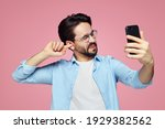Small photo of Man un-hygienically cleaning ear using finger with ticklish expression while using a smartphone