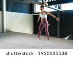 Small photo of Strong young woman in activewear jumping in a cardio workout at the gym. Beautiful latin woman doing burpees during a HIIT training