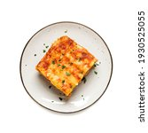 Small photo of Portion of ground beef lasagne topped with melted cheese and garnished with fresh parsley served on a gray plate . top view. isolated on white background