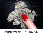 Finger woman with elegant red nail polish crushes a silver eyeshadow on a blackboard. Manicure and makeup concept - stock photo