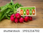Small photo of Sustainability Rating label on radishes with high, med and low ratings for food carbon footprint, water use, land use, packaging waste and chemical waste label. Consumer environmental rating label.