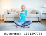 Small photo of Senior woman doing warmup workout at home. Fitness woman doing stretch exercise stretching her arms - tricep and shoulders stretch . Elderly woman living an active lifestyle.