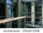 Small photo of Scaffolding installed in building support worker for safety in workplace. Man stands on scaffold board. Concept of scaffolding construction, scaffold, safety.