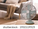 Small photo of Modern electric fan on wooden table in living room. Space for text