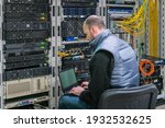 Small photo of A man with a laptop sits in a server room. A technician works near the racks of a modern data center. The system administrator configures the computer hardware.