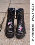 Small photo of A pair of rough black lace-up shoes stand on the concrete floor, on each shoe is a pink violet flower, a symbol of the juxtaposition of roughness and tenderness, love will save the world. Front view.