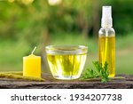 Small photo of Citronella (Scent Geranium). Pelagorium Citrosum essence oil in a cup with a candel incence and spray bottle. Over a wood plank with green blurre3de background and copy space.