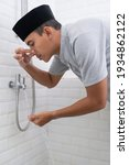 Small photo of Young Muslim man perform ablution wudhu before prayer at home