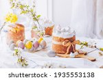 Small photo of Traditional ukrainian easter cake with white swiss meringue. New cruffin cake trend 2021. Spring cherry blossom and colorful painted eggs. Person decorates cake with hand. Free copy space.