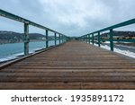 A wide worn brown wooden boardwalk with a green wood rail. There are a blue ocean and a treed mountain on one side and snow and a rocky area on the other side.  The sky is covered in grey clouds.