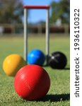 Small photo of In the foreground focus is on a red croquet ball in close up while in soft focus in the background are the red, blue and black croquet balls and the croquet hoop on a green croquet lawn.