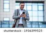 Small photo of Young businessman on the way to the office searching information on the internet with smartphone. Business, education, lifestyle concept