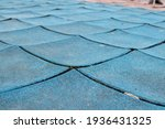 Small photo of broken rubber tiles in the playground, old Poured-in-Place, PIP, tartan surface, tartan track, warped, damaged, worn out