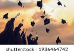 Small photo of Congratulations. Low angle view of happy young graduates in black robes throwing up their academic hats against the backdrop of a magical sunset. Concept of graduation and a new stage in life. Banner.