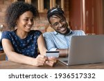 Small photo of Paying online. Smiling young married couple of afro american ethnicity provide payment via electronic bank app from home office. Happy black spouses buy goods service at web use money on prepaid card