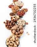 Small photo of Assortment of nuts in bowls. Cashews, hazelnuts, walnuts, pistachios, pecans, pine nuts, peanuts, macadamia, almonds, brazil nuts. Food mix on white background, top view, copy space