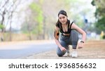 Small photo of Smiling fitness woman tie shoelaces getting ready for jogging outdoors.