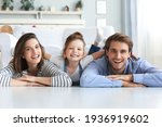 Small photo of Young Caucasian family with small daughter pose relax on floor in living room, smiling little girl kid hug embrace parents, show love and gratitude, rest at home together