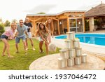 Small photo of Group of cheerful young friends having fun playing the knock down tin cans by throwing a ball game while at poolside summertime outdoor party